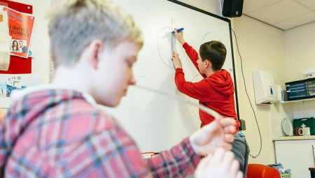 autistic child drawing on whiteboard